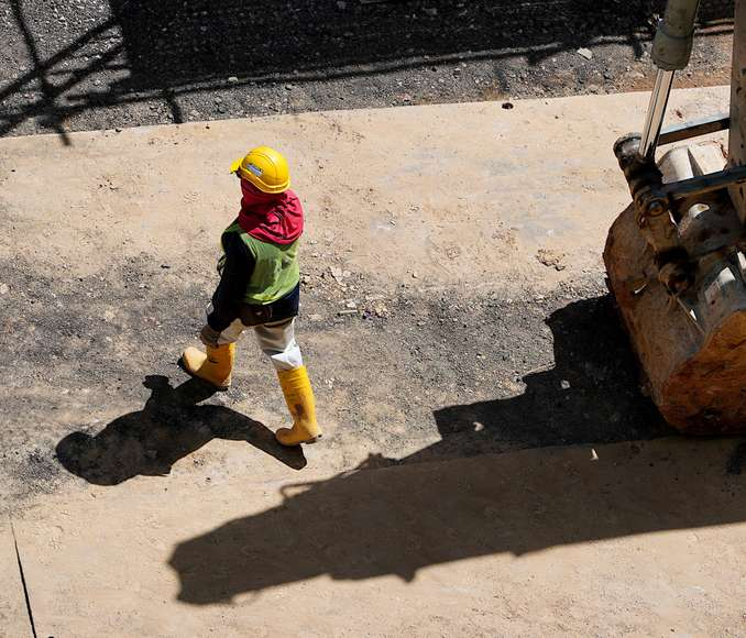 Arial view of worker in hardhat walking next to a forklift